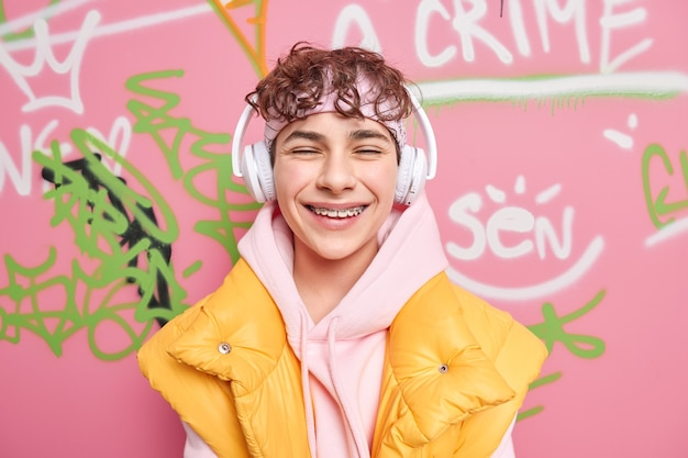 Positive curly haired youngster smiles gladfully has braces on teeth dressed in hoodie with vest enjoys favorite music via wireless headphones draws graffiti on street walls without permission