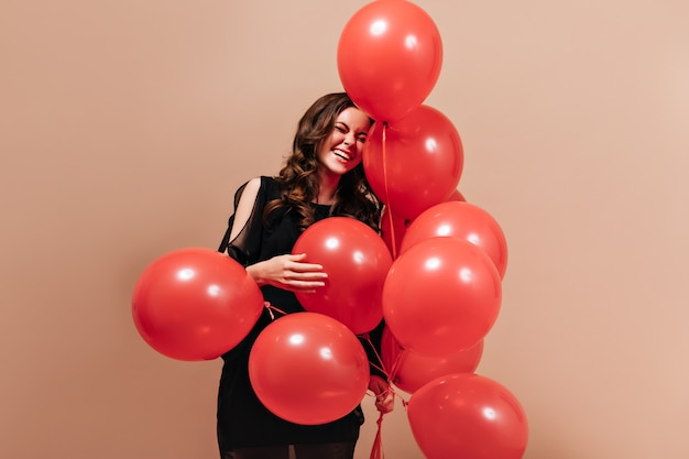 Positive curly woman in black outfit laughs and poses with red balloons on isolated background.