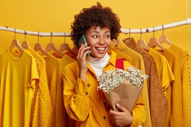ポジティブな巻き毛の女性は電話で会話し、携帯電話を耳の近くに保ち、美しい花束を持っています