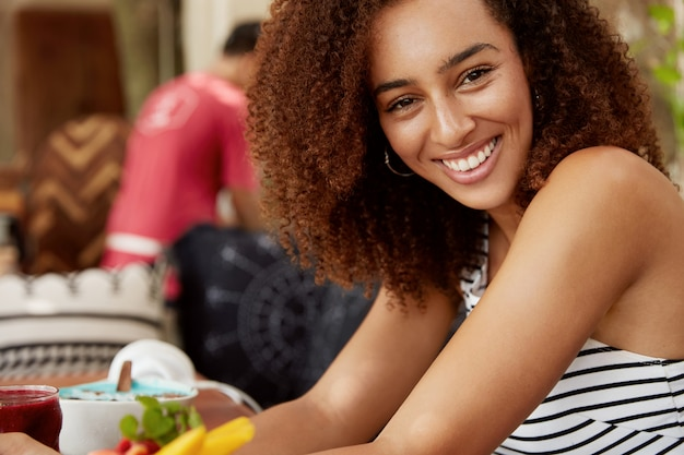 Positive curly young woman with dark healthy skin, smiles pleasantly, sits at cafe table surrounded with delicious dish, enjoys recreation time in restaurant. people, lifestyle and ethnicity concept