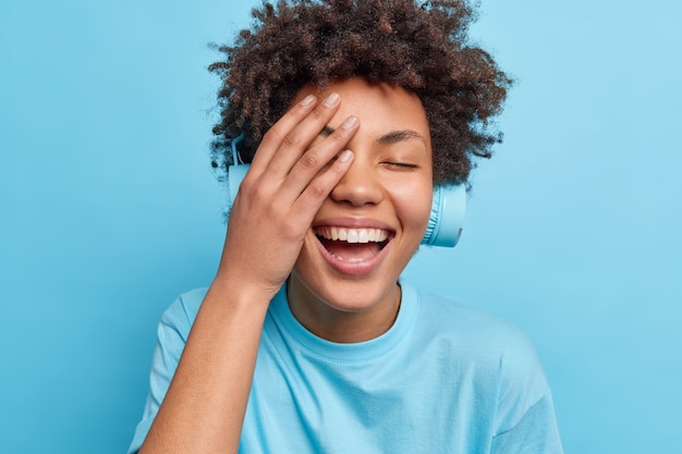 긍정적 인 곱슬 머리 여자는 행복하게 얼굴 손바닥 미소를 만든다 평온한 표정이 파란색 벽 위에 고립 된 캐주얼 티셔츠를 입은 헤드폰을 통해 오디오 트랙을 수신합니다. 감정 라이프 스타일