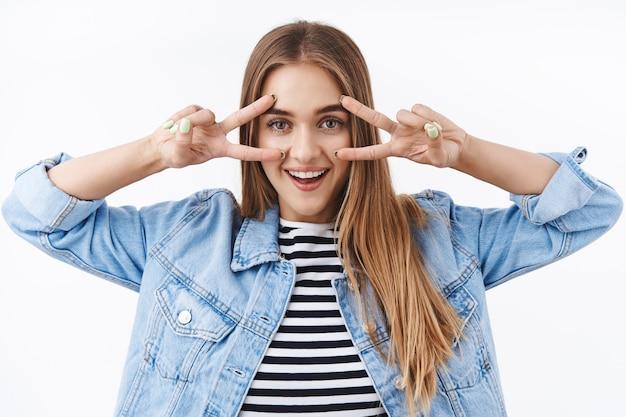 デニムジャケットのポジティブなかわいい金髪の女性、指にカラフルなマニキュアで平和のジェスチャーを示し、嬉しそうに笑って、カワイイポーズをとって、幸せとのんきな感情を表現します