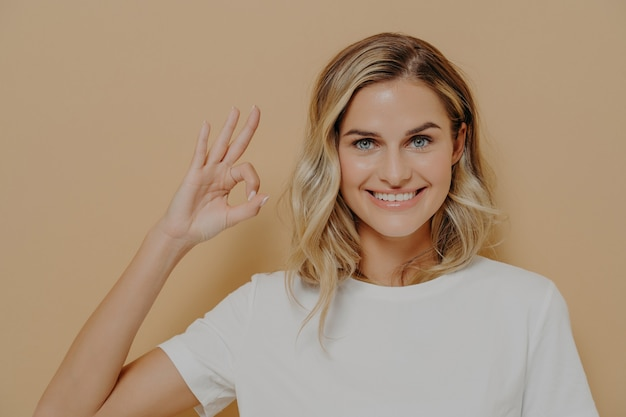 Positive cute blonde young woman in white tshirt shows ok sign with one hand, smiling happily at camera, female showing everything is super and fine. body language and human emotions