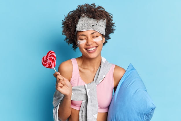 Positive cute curly haired woman smiles broadly enjoys relaxing morning routines has healthy long sleep poses with lollipop poses in nightwear with pillow indoor isolated over blue wall