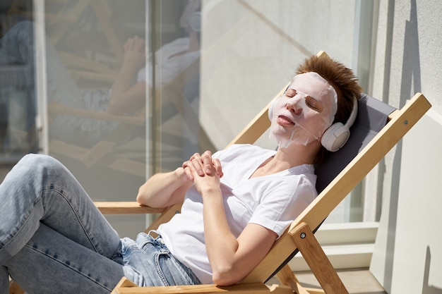 Positive cute girl with stylish hairstyle sitting on the balcony, applying facial mask on face.