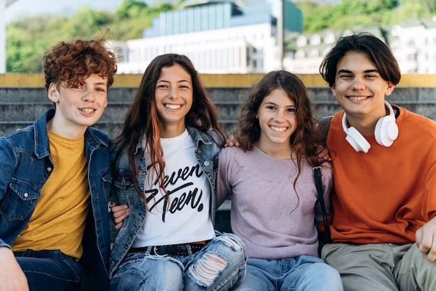 긍정적이고 귀여운 십대들은 벤치에 앉아 카메라를 보고 미소를 짓습니다. 귀여운 소년과 소녀, 야외에서 학생