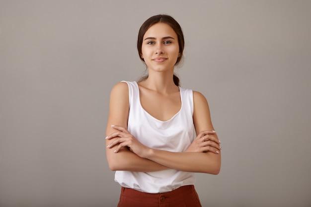 彼女の胸に自信を持って腕を組んで、あなたの広告コンテンツのためのコピースペースで塗りたての空白の壁のある空のアパートで喜んでポーズをとって笑顔のポジティブなかわいい若いヨーロッパの女性