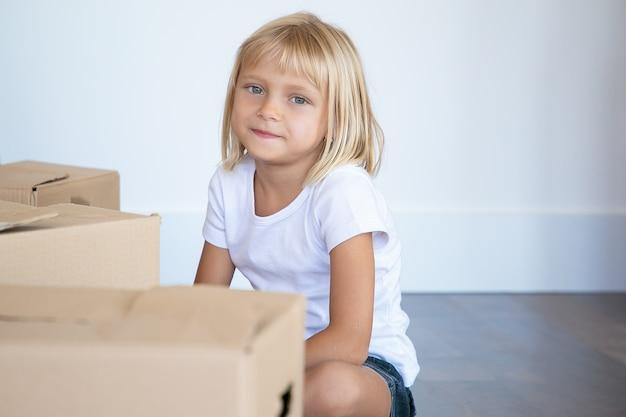 Bambina capelli biondi più carina positiva che si siede sul pavimento vicino a scatole di cartone animato nel nuovo appartamento e guardando dentro