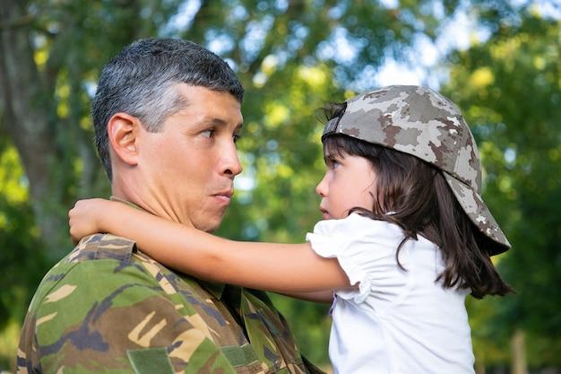 迷彩服を着たポジティブなお父さんが、軍のミッション旅行から戻った後、気分を害した娘を腕に抱き、屋外で女の子を抱きしめています。クローズアップショット。家族の再会または帰国の概念