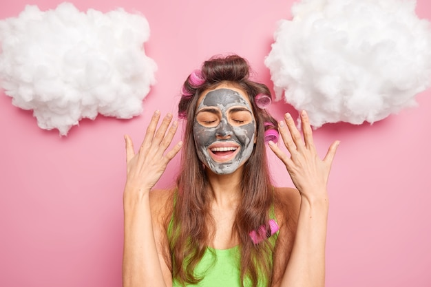 Positiva ragazza dai capelli scuri indossa bigodini maschera facciale di argilla tiene gli occhi chiusi sorrisi alza delicatamente le mani gode di procedure di bellezza si prepara per un'occasione speciale isolato sopra il muro rosa