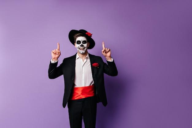 멕시코 스타일의 옷을 입은 긍정적 인 검은 머리의 남자는 텍스트를위한 공간으로 초상화를 위해 포즈를 취하면서 손가락을 위쪽으로 즐겁게 보여줍니다.