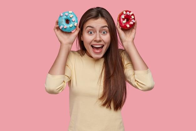 La giovane donna dai capelli scura positiva tiene due ciambelle dolci, tiene la bocca ampiamente aperta