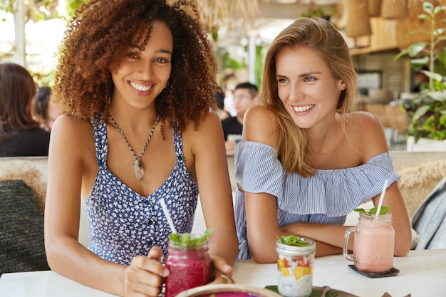 Positive dark skinned african american female drinks cold smoothie, meets with best friend in cozy restaurant, have glad expressions, share news with each other and plans on coming holidays.
