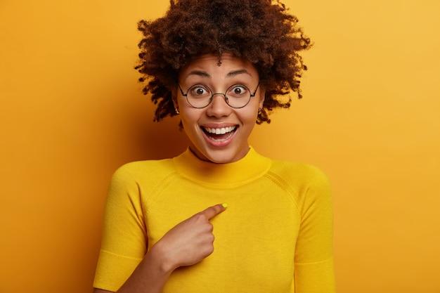 ポジティブなダークスキンのアフロアメリカンの女性は自分自身を指さし、誰に選ばれたか、勝ったかを尋ね、明るい黄色の服を着て、屋内でポーズをとります。幸せな反応、良い感情と感情。