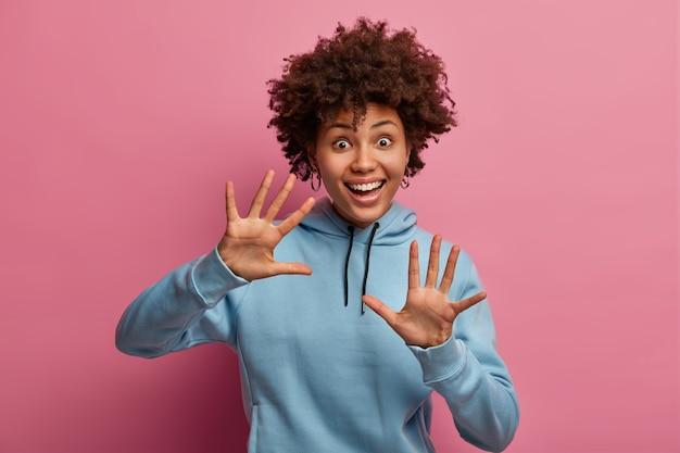 La donna afroamericana dalla pelle scura positiva alza i palmi, ride allegramente, ha gli occhi ben aperti, reazione felice, umore giocoso, ride positivamente, indossa una felpa blu, isolata sul muro rosa.