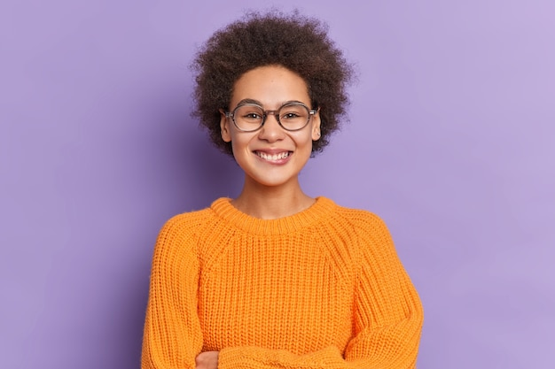 덥수룩 한 아프로 머리를 가진 긍정적 인 어두운 피부의 아름다운 십대 소녀는 니트 오렌지 스웨터와 안경을 행복하게 입고 미소 짓습니다.