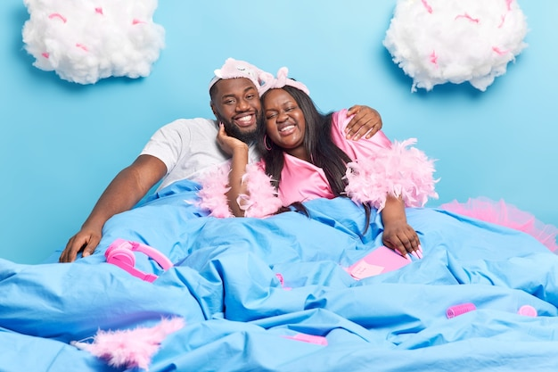 침대에서 긍정적 인 어두운 피부 커플 포옹 서로 사랑 집에서 함께 시간을 보내는 것을 즐긴다 게으른 하루는 파란색에 광범위하게 고립 된 미소