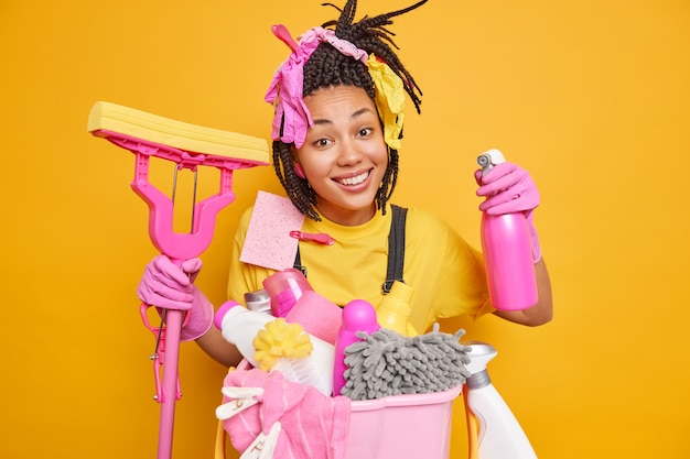 Positive dark skinned ethnic woman with dreadlocks holds detergent and mop