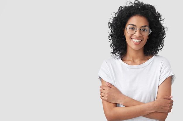 Позитивная темнокожая самка с зубастой улыбкой, застенчивым выражением лица, держит руки на груди, выглядит счастливо, рада крестьянскому разговору с другом, изолирована на белой стене