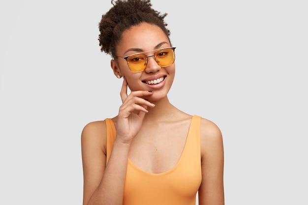 トレンディなサングラス、カジュアルなベスト、白い完璧な歯を持ち、壁の上に立って、幸せを表現するポジティブなダークスキンの女性モデル。幸せな若いアフリカ系アメリカ人女性モデル屋内