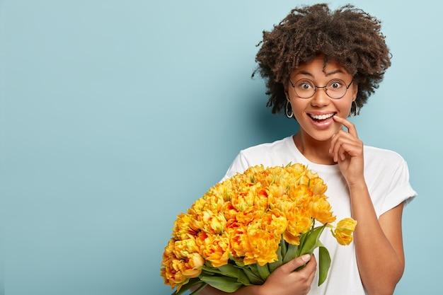 행복한 놀란 표정으로 긍정적 인 어두운 피부 여성 모델, 이빨 미소가 있습니다.