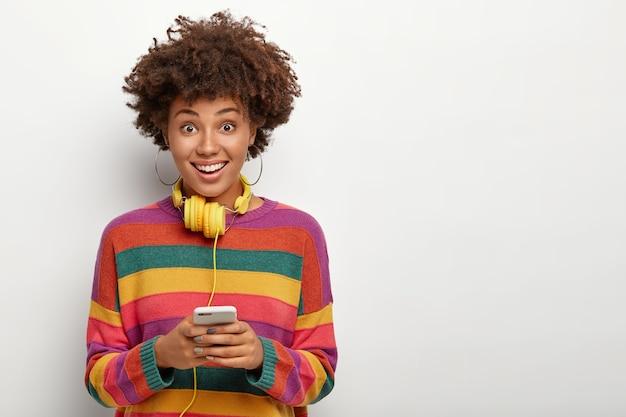 ポジティブなダークスキンの女の子は、ヘッドフォンで音質をチェックし、音楽を聴き、縞模様のセーターを着て、白い背景の上でポーズをとります。