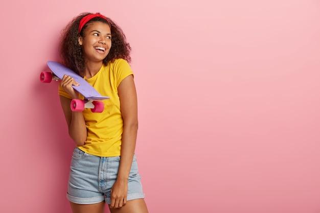 La ragazza dalla pelle scura positiva tiene lo skateboard viola, distoglie lo sguardo