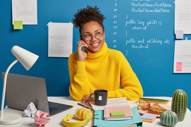 Positive dark skinned girl makes telephone call, discusses improvement and developing business project, dressed in yellow sweater, looks aside, poses against blue background