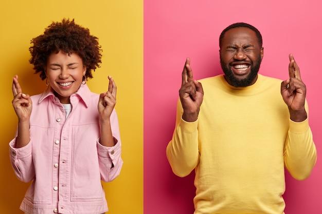 Позитивные темнокожие подруга и парень скрещивают пальцы, загадывая желание, счастливо улыбаются и молятся об удаче