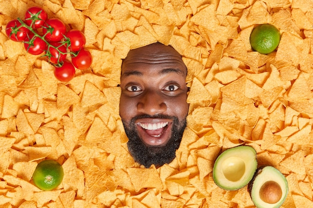 Positive dark skinned guy with thick beard smiles happily buried in nachos potato chips surrounded by tomatoes lime and halves of avocado feels very happy