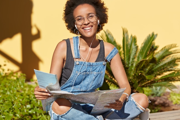 Positive dark skinned lady with afro hairstyle, holds map, enjoys trip on vacation, wants to reach some destinations, wears casual overalls, models outdoor in tropical setting. people and traveling