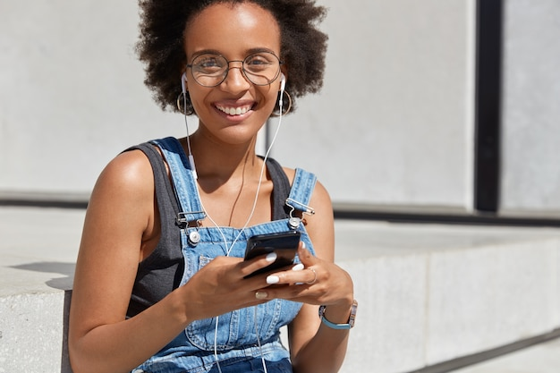 Positive dark skinned lady with toothy smile, listens audio at digital cellular, being happy to hear favourite song, enjoys pure sound, wears round spectacles and casual clothes, poses outside