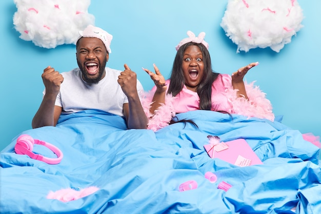 Positive dark skinned man clenches fists and exclaims loudly poses near his puzzled afro american wife in bed