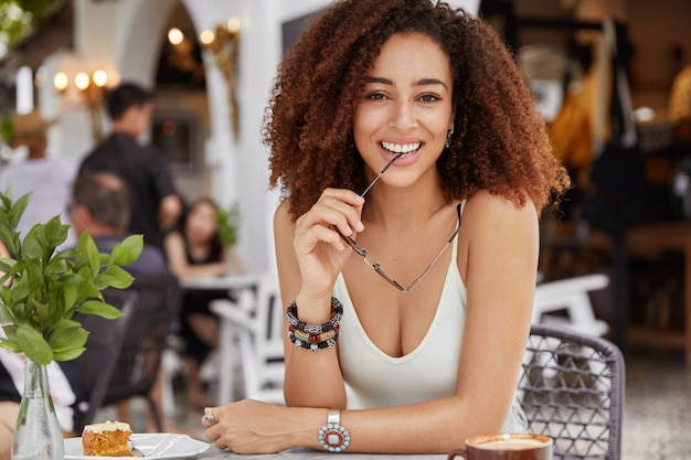 Positive dark skinned mixed raced female with curly bushy hairstyle holds eyewear in hands, wears casual t shirt, has lunch or coffee break in cafe