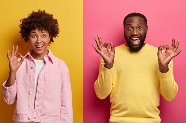 La donna e l'uomo sorridenti dalla pelle scura positiva mostrano gesti giusti con espressioni assertive soddisfatte, promuovono un articolo o raccomandano un prodotto di acquisto, forniscono un feedback eccellente, valutano qualcosa di fantastico