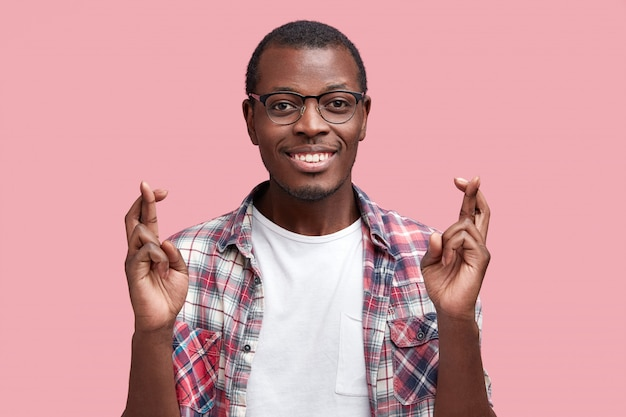 Positive dark skinned student wonk crosses fingers before passing exam, dressed in casual checkered shirt, has happy expression