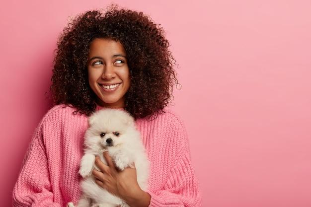 아프로 덥수룩 한 헤어 스타일을 가진 긍정적 인 어두운 피부의 십대 소녀, 분홍색 스튜디오에서 흰색 스피츠로 포즈를 취하고 자연에서 피크닉을 갖는 것에 대해 생각합니다.