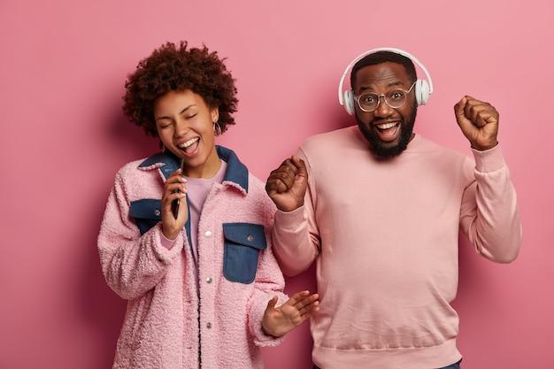 긍정적 인 어두운 피부를 가진 여자와 남자는 음악의 리듬으로 즐겁게 춤을 추고, 주먹을 쥐고, 스마트 폰 장치에서 노래합니다.