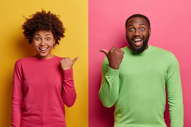 긍정적 인 어두운 피부의 여성과 남성은 엄지 손가락으로 서로를 가리키고, 기본 옷을 입고, 기분이 좋으며, 노란색과 분홍색 벽에 고립 된 친구를 선택하도록 제안합니다. 내 동반자를보세요.