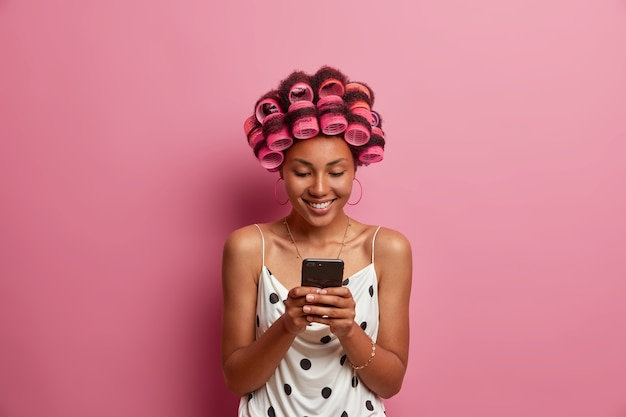 Positive dark skinned woman applies hair rollers for making perfect hairstyle holds modern cellphone