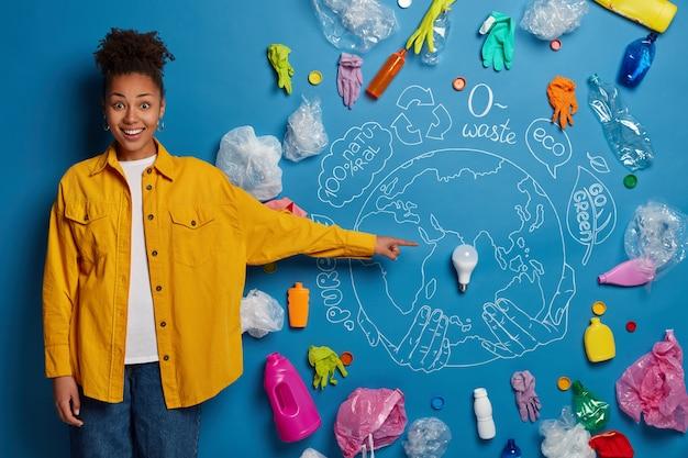 Una donna dalla pelle scura positiva dimostra il suo piano per pulire la terra, punta il bulbo luminoso al centro del pianeta, indossa una camicia gialla, preoccupata della conservazione dell'ambiente.