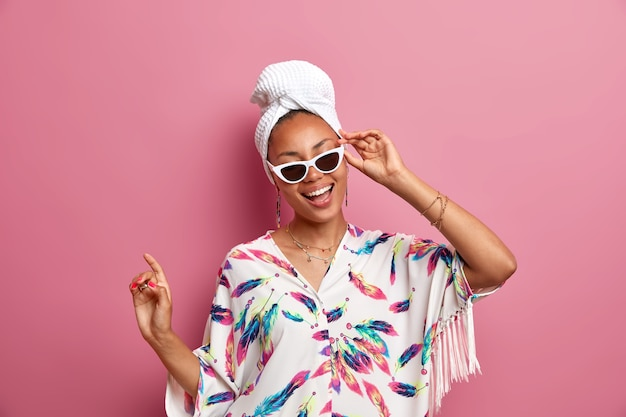 Positive dark skinned woman dressed in domestic gown wears sunglasses bath towel on head feels refreshed after taking shower has healthy skin smiles broadly dances over pink wall being at home