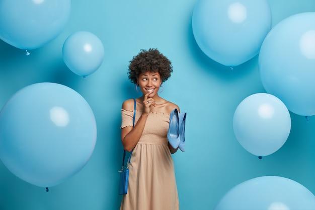 Positiva donna dalla pelle scura vestita in un elegante abito lungo, sceglie scarpe blu per adattarsi alla borsa, vestiti per avere un aspetto favoloso alla festa corporativa, sta contro il muro blu, volano palloncini intorno