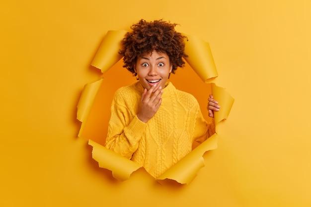 긍정적 인 어두운 피부를 가진 여자는 종이 배경의 찢어진 구멍을 통해 행복하게 놀란 반응을 보입니다.