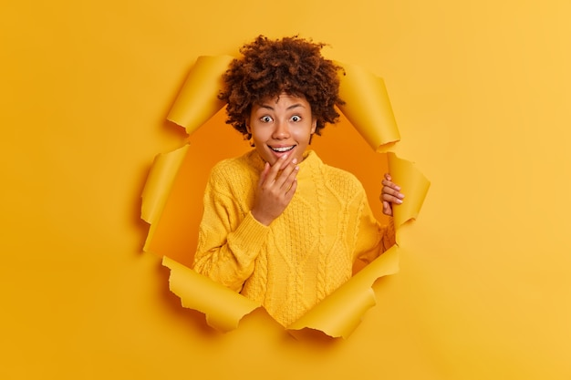 Positive dark skinned woman has happy surprised reaction through ripped hole of paper background