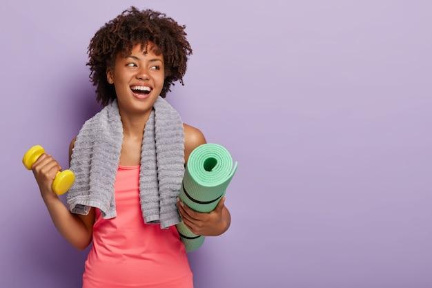 긍정적 인 어두운 피부를 가진 여자는 요가 매트와 아령을 들고, sportcloths를 착용하고, 목에 수건을 가지고 있습니다.
