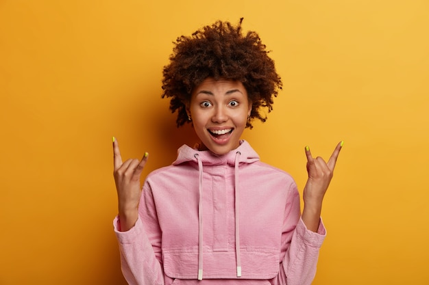 ポジティブな浅黒い肌の女性がロックサインを作り、ロックンロールジェスチャーを示します
