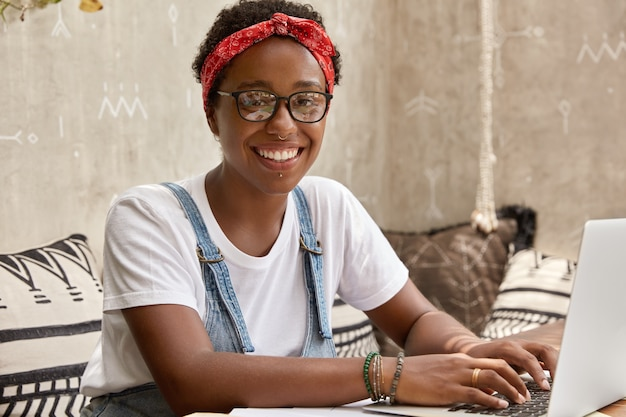 Positive dark skinned woman manager smiles gladfully, prepares working schedule for employee