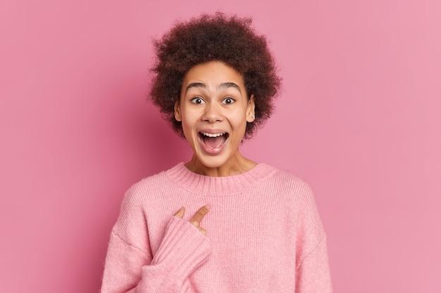 La donna dalla pelle scura positiva indica se stessa con un'espressione felicissima ha uno sguardo divertente