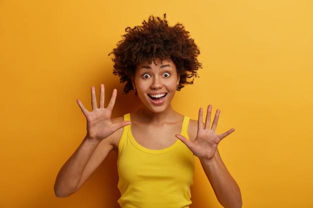 긍정적 인 어두운 피부를 가진 여성은 손바닥을 들고 즐거운 느낌을 가지고 장난스런 분위기를 가지고 있으며 재미있는 표정으로 응시하고 캐주얼 셔츠를 입고 노란색 벽 위에 격리됩니다. 사람, 감정 및 행복 개념